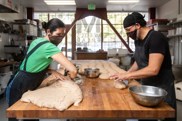 Tamsen Fynn and Eduardo Morell work dough into loaves at Morrel's bread making kitchen