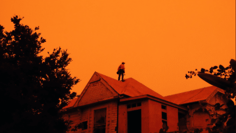a man standing on the roof of a house in orange light