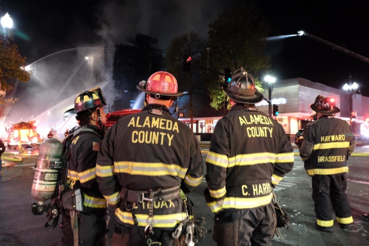 Firefighters from Alameda County and Hayward watch as the fire continues to burn at 2067 University Avenue. Nov. 21, 2020. Photo: Pete Rosos