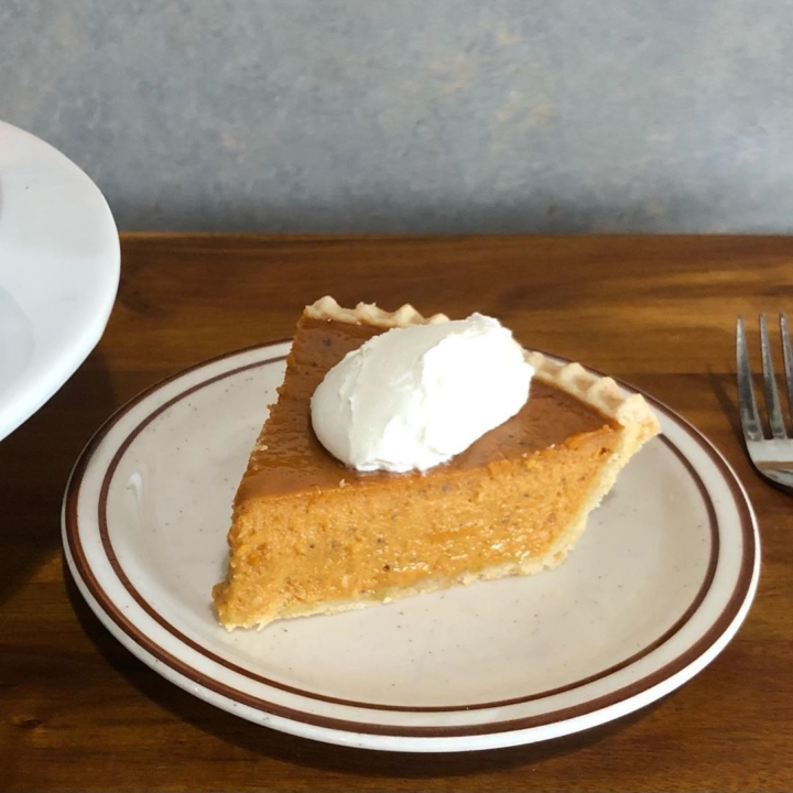 A slice of pumpkin pie on a plate with whipped cream.