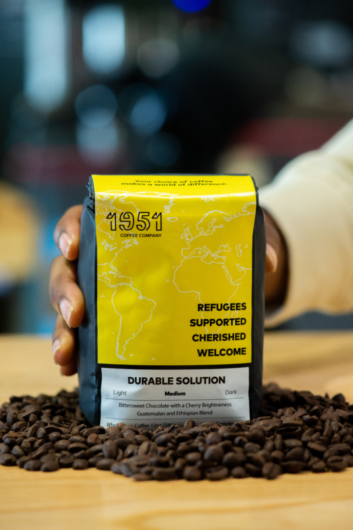 A hand holds a bag of Durable Solution Roast from 1951 Coffee Company sitting in a pile of loose coffee beans.