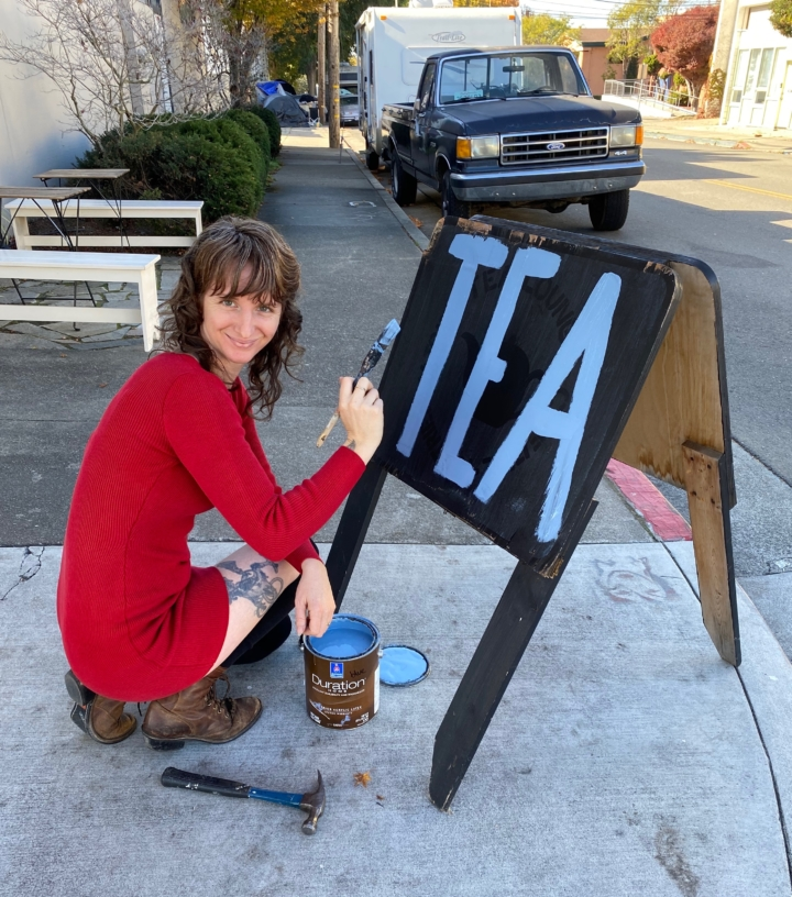 """Blue Willow Tea owner Ali Roth kneels down to paint the word """"Tea"""" on a sandwich board"""