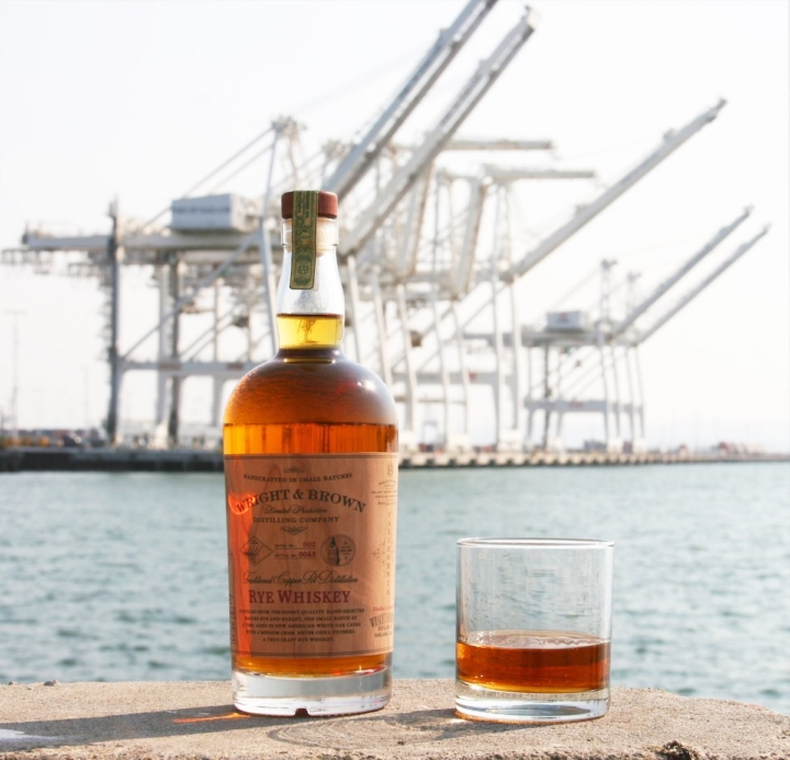 A bottle of Wright & Brown rye whiskey and a glass filled part way with spirits sits on a surface with the Port of Oakland in the background.