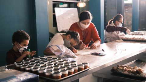 Two of Oakland Bloom's chefs, Sanel Mlivo (in red, with her children Aaron and Layla) and Kit Lam, preparing the to-go orders for the day. Credit: Pete Rosos