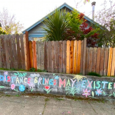 """April Distance Brings May Existence,"" chalked onto a wall outside a house in Berkeley"