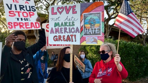 People hold up signs at an AntiAsianHate Rally in Albany on march 25
