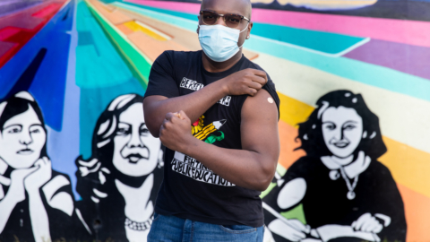 Marvin Reed, a third-grade teacher at Thousand Oaks Elementary, poses in front of a mural outside of the school after getting the second dose of the COVID-19 vaccine. March 10, 2021.