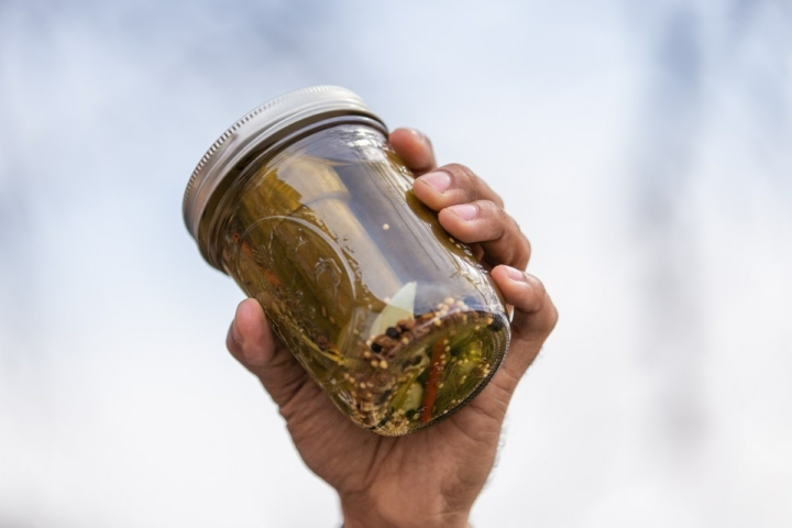 A hand holds up a Mason jar of pickles.