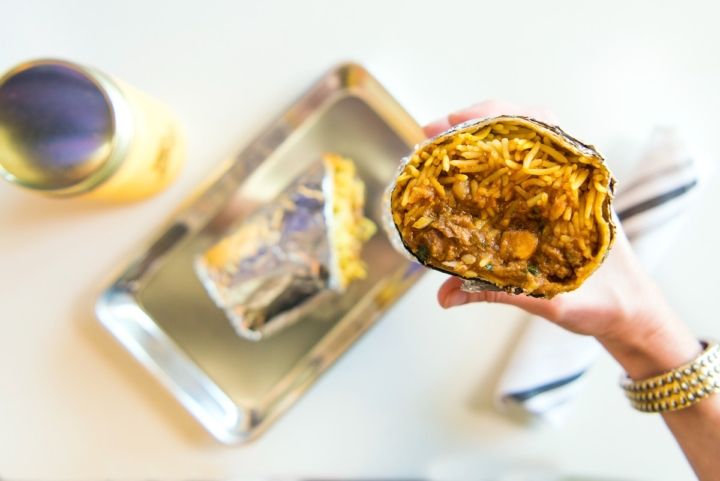 A hand holds up a Chicken Tikka Burrito over a silver tray.