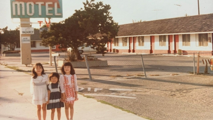 Three young girls in front of motel sign