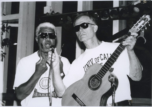 two men in a band, one singing, one playing the guitar