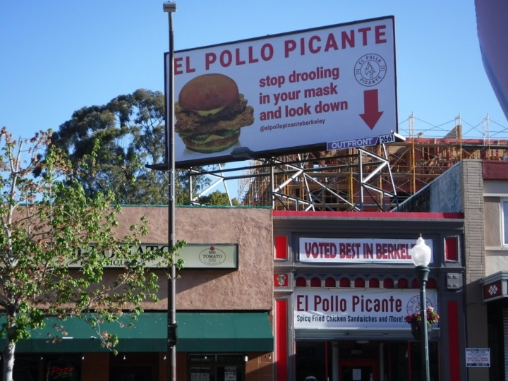 A billboard for El Pollo Picante points to the Berkeley restaurant that is now serving spicy fried chicken sandwiches.