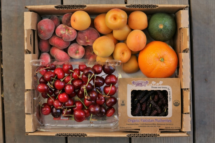 A CSA box filled with stone fruit from Frog Hollow Farm