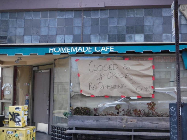 """A handwritten sign that reads """"Closed for Upgrades Reopening Soon"""" hangs in the window at Berkeley's Homemade Cafe."""