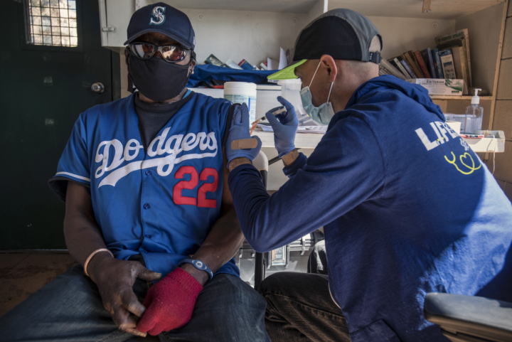 Man in Dodgers shirt getting a vaccination.
