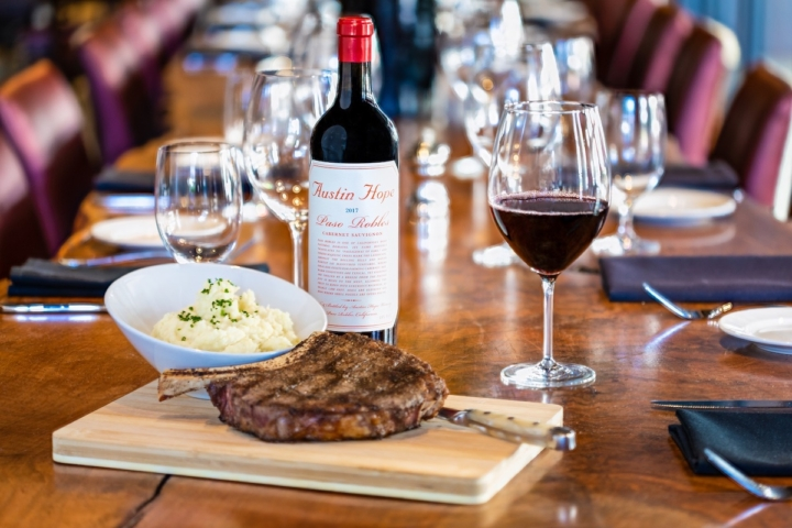 A set table featuring a bottle of wine, a bowl of mashed potatoes and a steak on a cutting board LB Steak. Credit: LB Steak