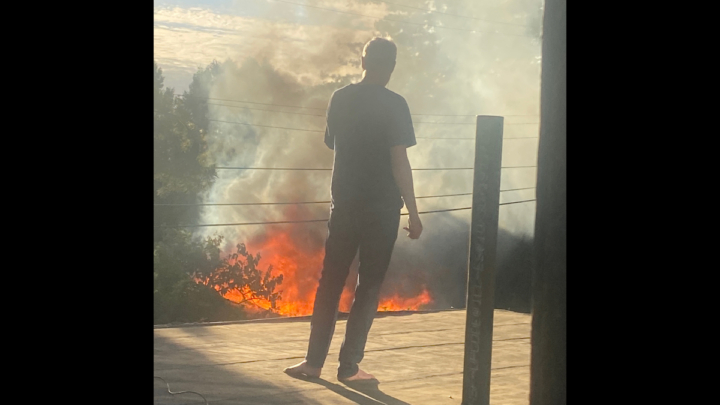 a man standing in a home and a view of the fire in the neighorhood beneath