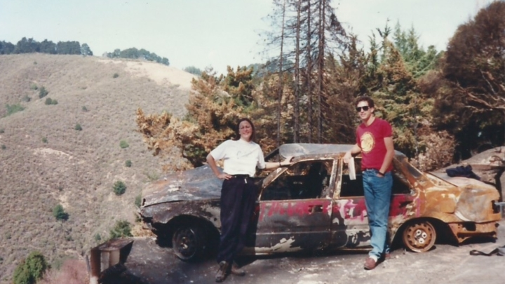 People standing in front of scorched car after the 1991 Berkeley-Oakland firestorm